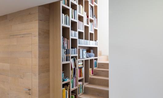 Gli spazi interni ruotano attorno ad una scala libreria, elemento di design e fulcro dell'abitazione