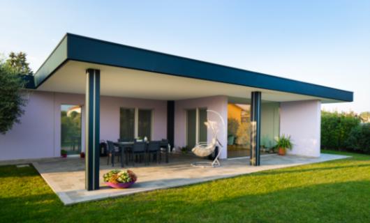 Ampio portico e grandi vetrate esaltano le caratteristiche progettuali di questa villa in legno.