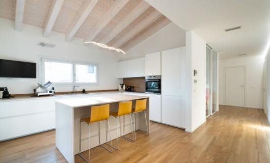In questa casa in legno la palette di colori chiari risalta l'eleganza della grande cucina