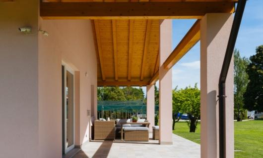 Il portico si affaccia verso il parco conferendo eleganza e semplicità a tutta la realizzazione.